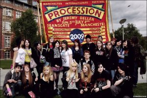 Process: An Exhibition feature Manchester goths. The exhibition was part of Manchester International Festival 2009. It feature various groups pcitured in front of the banner. Image: © BBC
